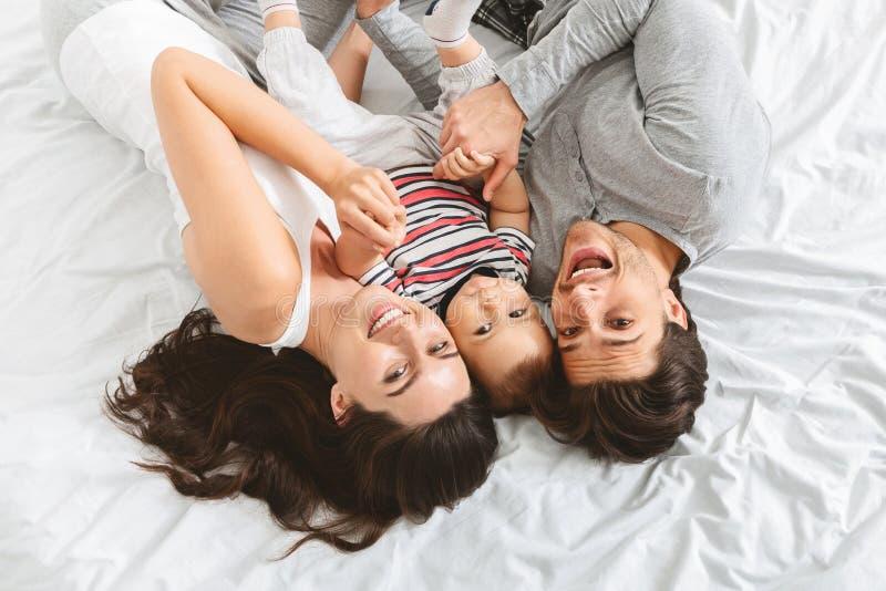 Bébé garçon adorable embrassant avec des parents dans le lit image libre de droits