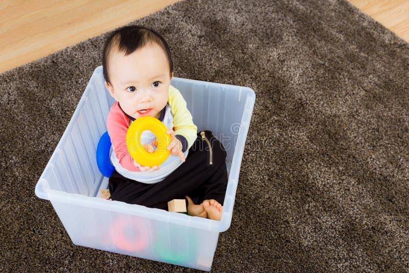 Bébé garçon asiatique jouant à l'intérieur de la boîte en plastique images stock