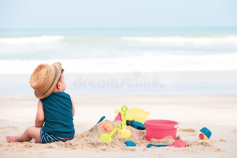 Bébé garçon asiatique jouant le sable sur la plage, photographie stock