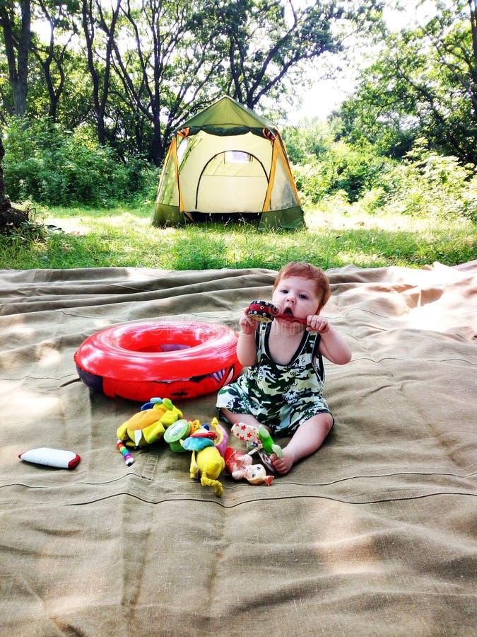 Bébé garçon avec des jouets se reposant à l'endroit de camping près de la tente photo libre de droits