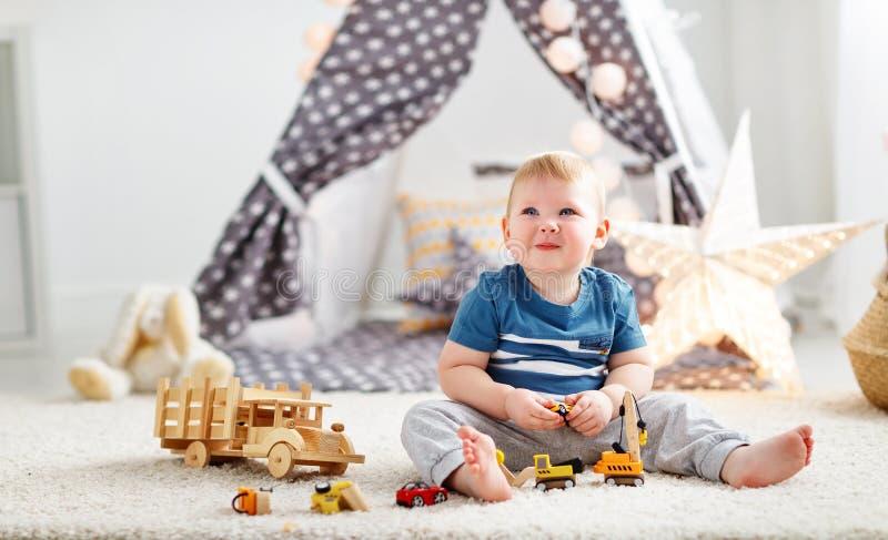 Bébé garçon avec des voitures de jouet chez la salle de jeux du ` s des enfants image libre de droits