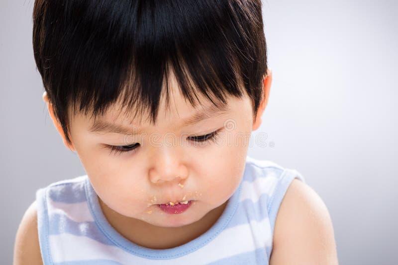 Bébé garçon avec la bouche sale et le regard vers le bas photos stock
