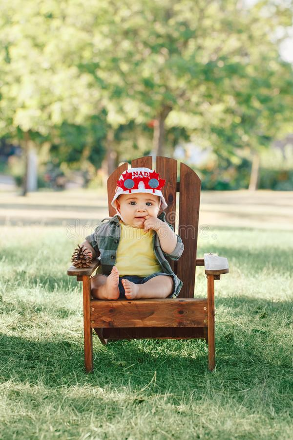 Bébé garçon caucasien portant le chapeau canadien et les lunettes drôles de feuille d'érable image libre de droits