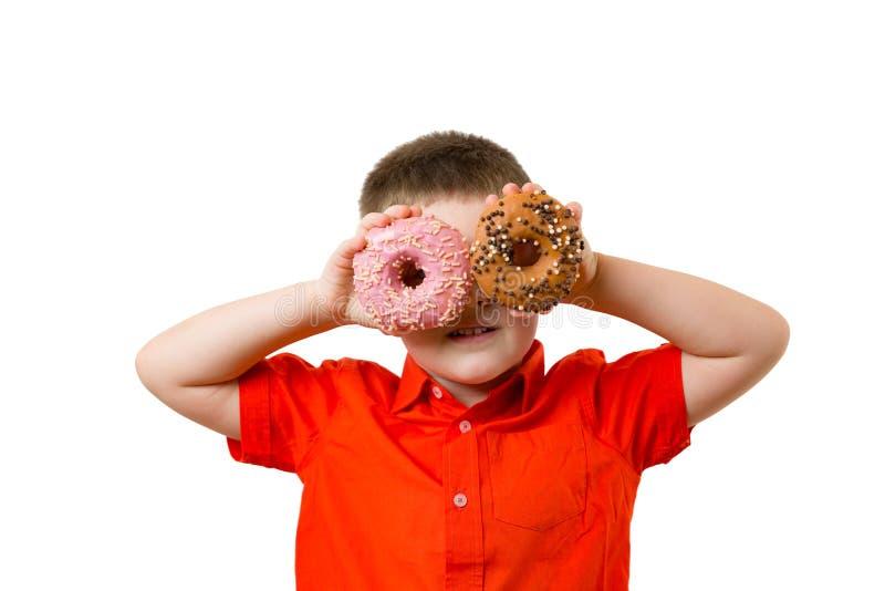 Bébé garçon d'élève du cours préparatoire avec deux butées toriques de turquoise sur ses yeux sur le mur blanc de fond L'enfant a photographie stock libre de droits
