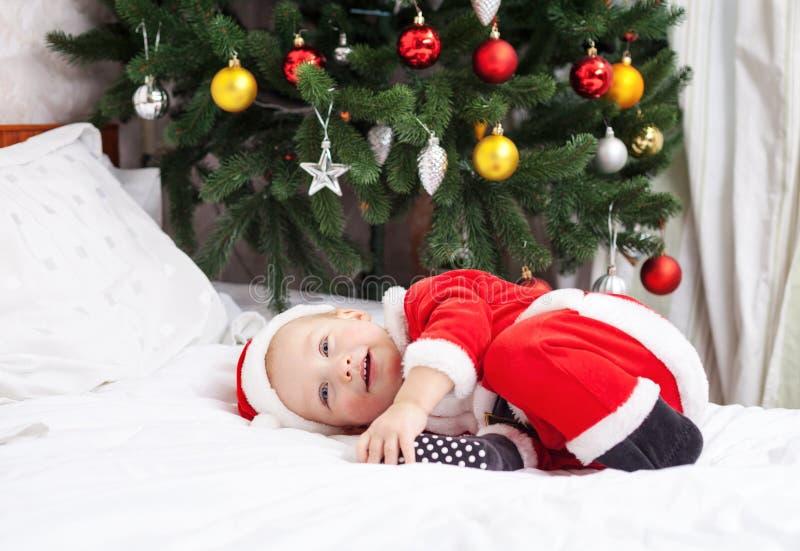 Bébé garçon dans le costume de Santa se trouvant sur le lit photos libres de droits