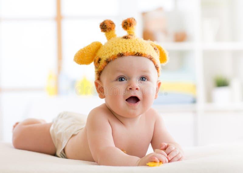 Bébé garçon dans un chapeau drôle de girafe se trouvant sur son ventre dans la crèche photo stock