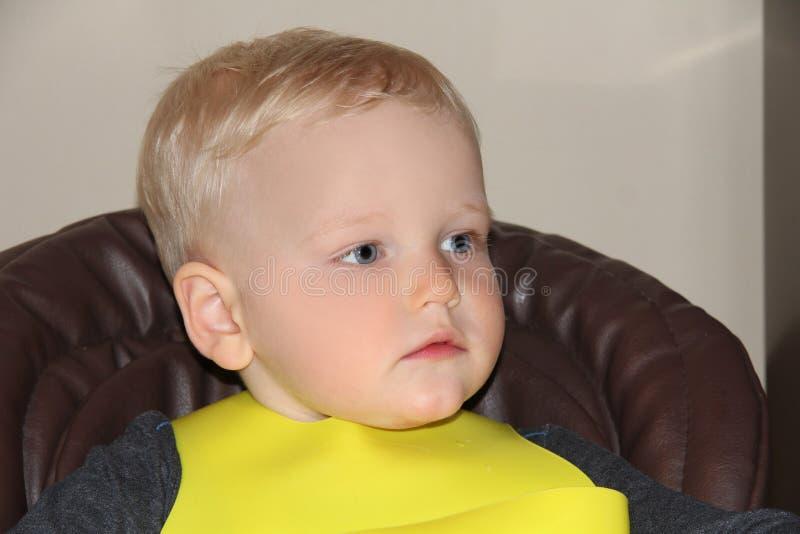 Bébé garçon de deux ans dans un highchair à la maison photo libre de droits