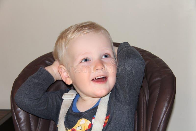 Bébé garçon de deux ans dans un highchair à la maison photos libres de droits