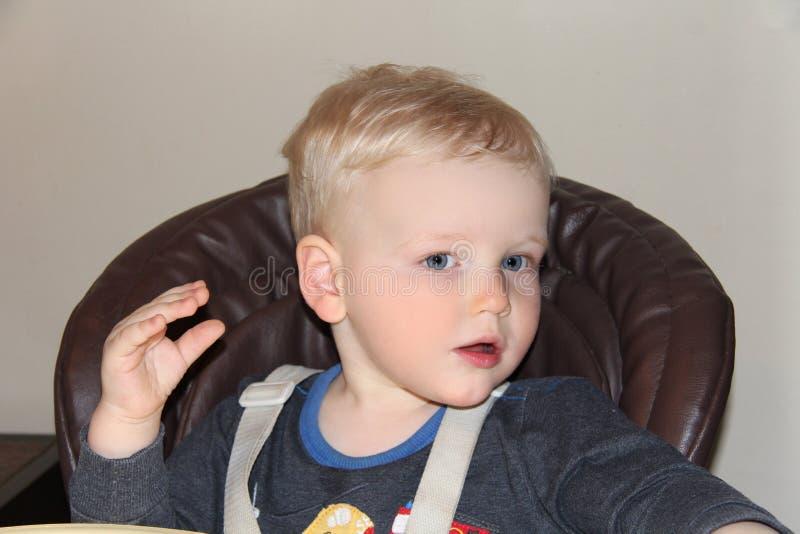Bébé garçon de deux ans dans un highchair à la maison image stock