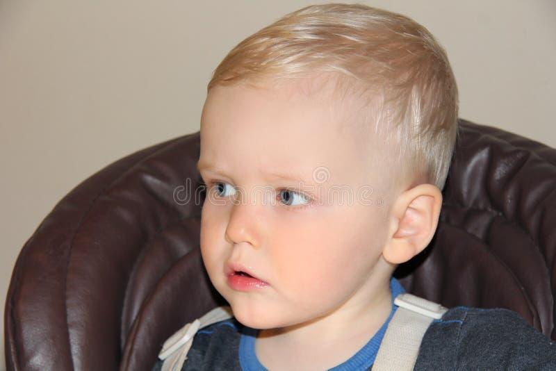 Bébé garçon de deux ans dans un highchair à la maison photo stock