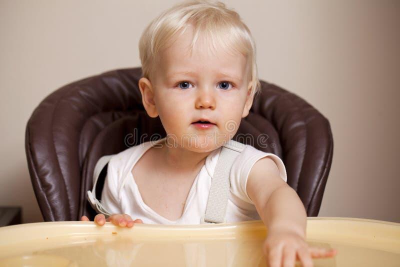 Bébé garçon de deux ans mangeant dans un highchair à la maison photographie stock