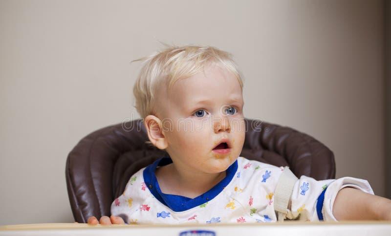 Bébé garçon de deux ans mangeant dans un highchair à la maison photographie stock libre de droits