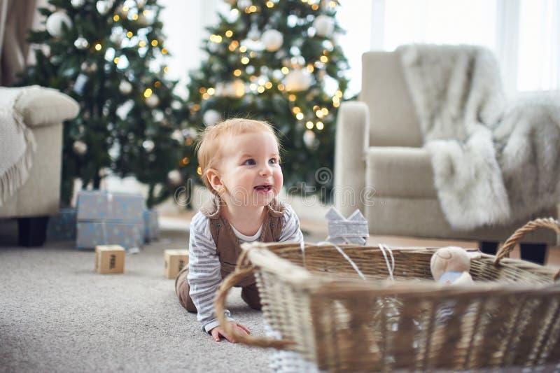 Bébé garçon de 1 an rampant sur le plancher à la maison décorations de Noël sur un fond photographie stock