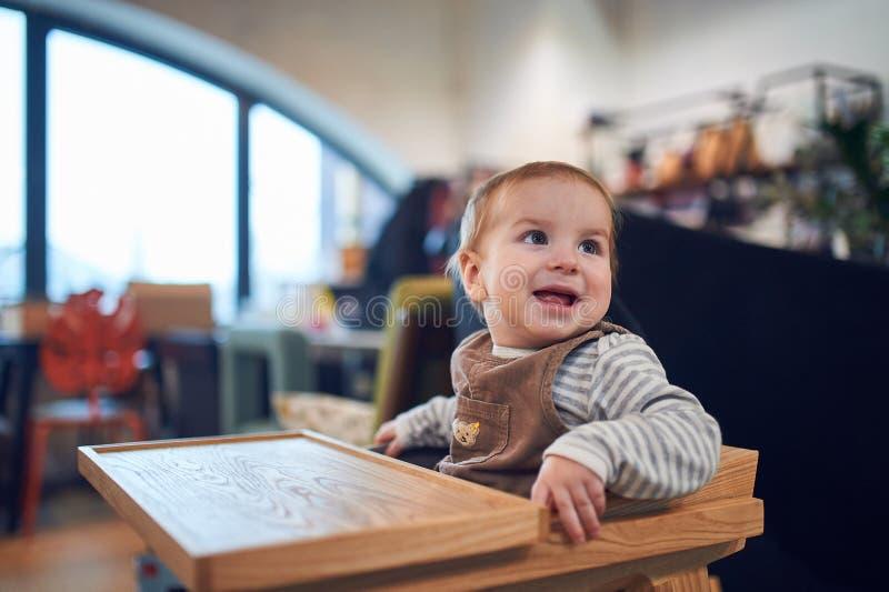 Bébé garçon de 1 an s'asseyant dans la chaise d'arbitre en bois à la maison image stock