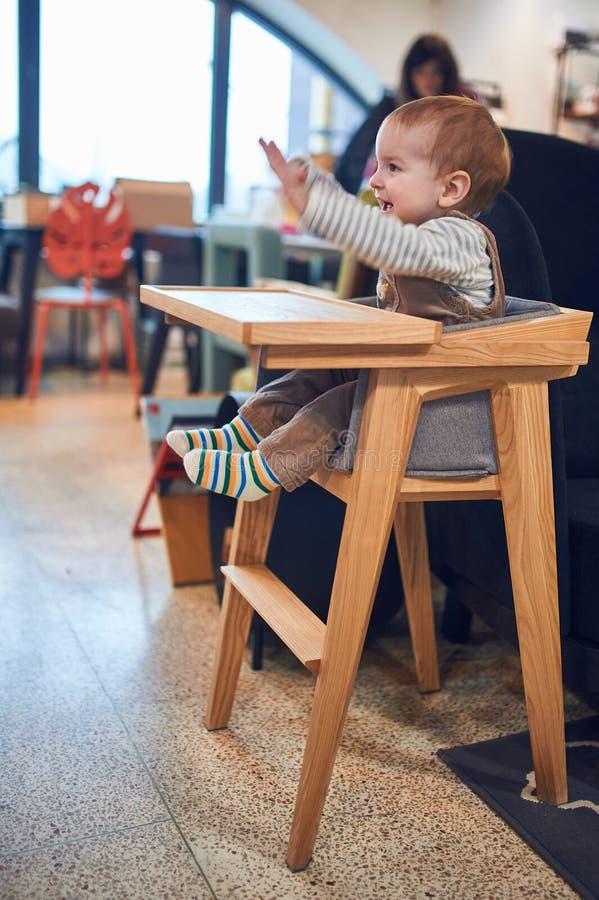 Bébé garçon de 1 an s'asseyant dans la chaise d'arbitre en bois à la maison photographie stock libre de droits