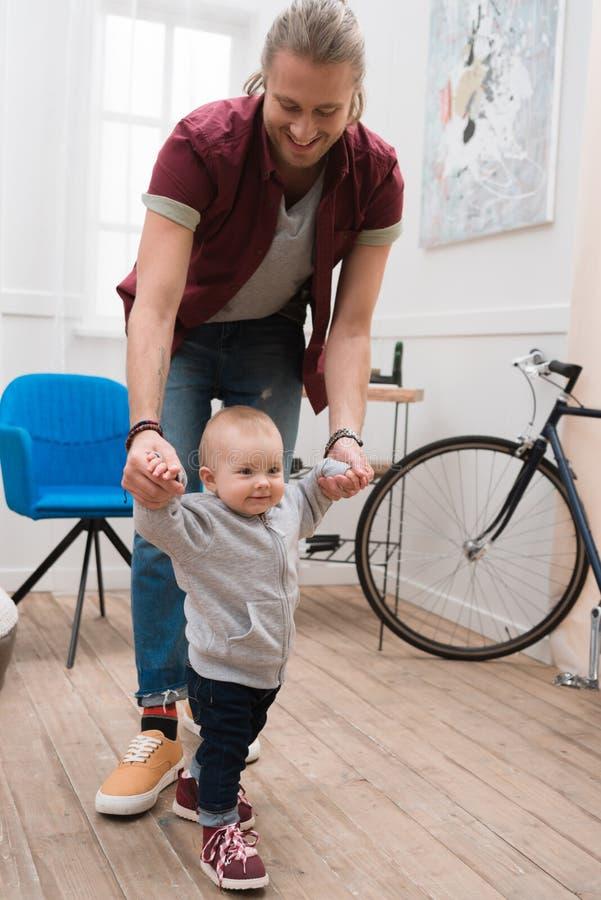 bébé garçon de sourire d'enseignement de père à marcher photo stock