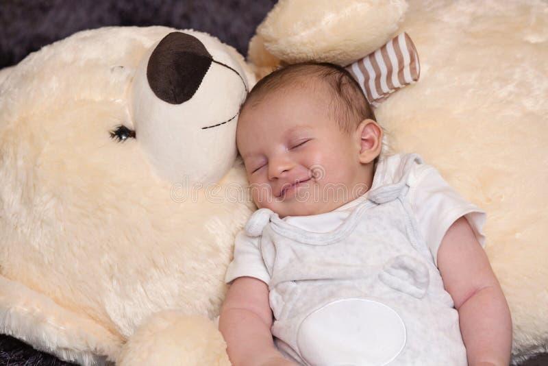 Bébé garçon de sourire dormant avec grand Teddy Bear image stock