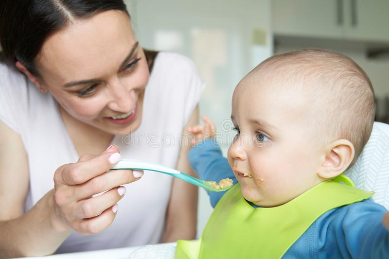 Bébé garçon de sourire de bébé de 8 mois à la maison dans la chaise d'arbitre étant Fed Solid Food By Mother avec la cuillère images libres de droits