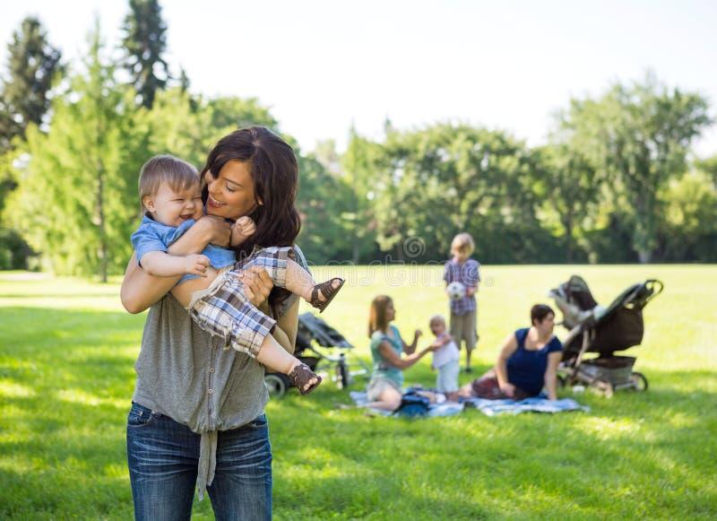 Bébé garçon de transport de jeune femme en parc photos libres de droits