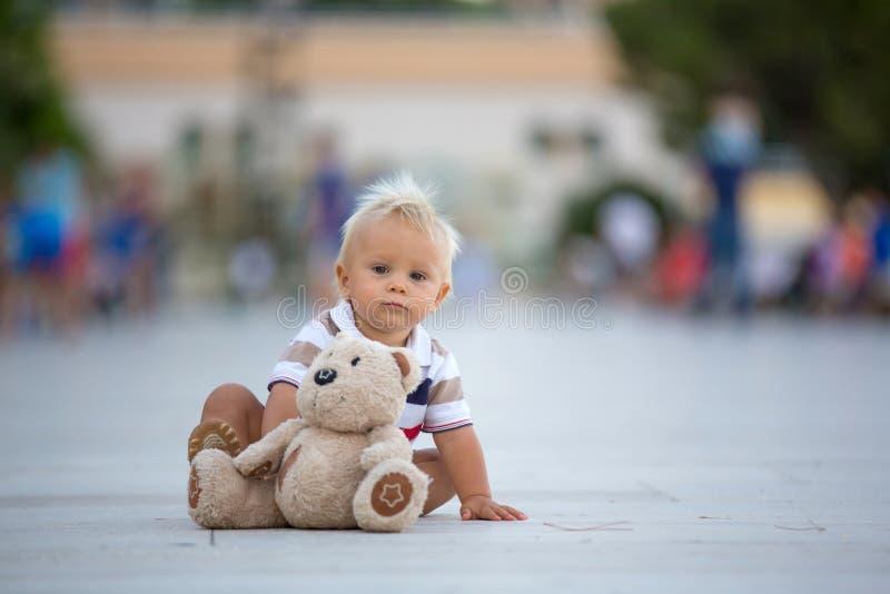 Bébé garçon doux d'enfant en bas âge, jouant avec l'ours de nounours dans la ville image libre de droits