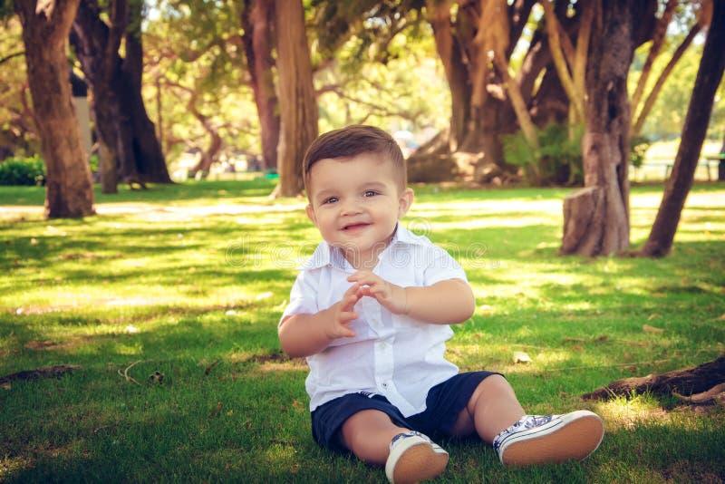 Bébé garçon doux s'asseyant en parc d'automne images libres de droits