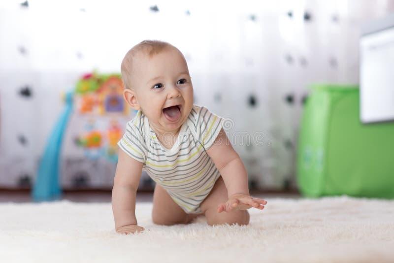 Bébé garçon drôle de rampement à l'intérieur à la maison photographie stock libre de droits