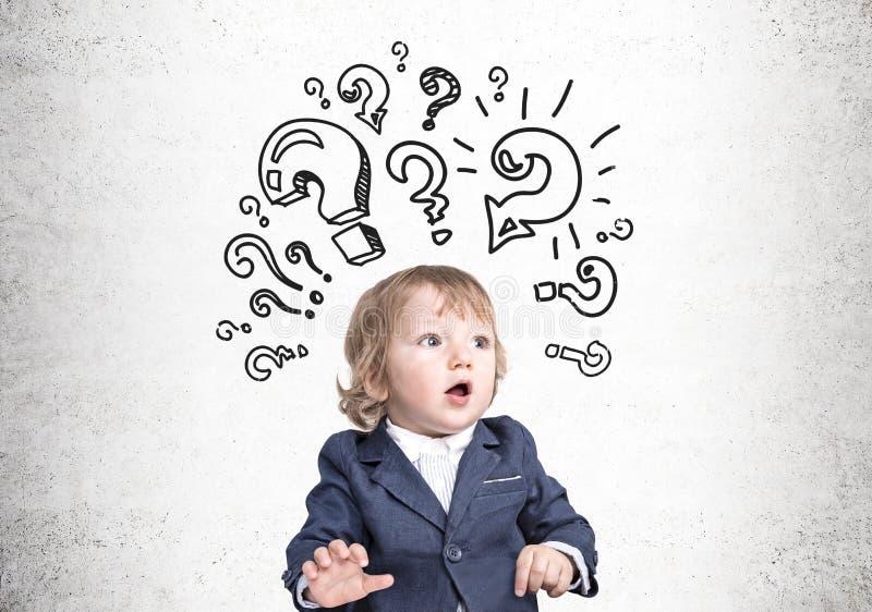 Bébé garçon et points d'interrogation sur le béton image libre de droits