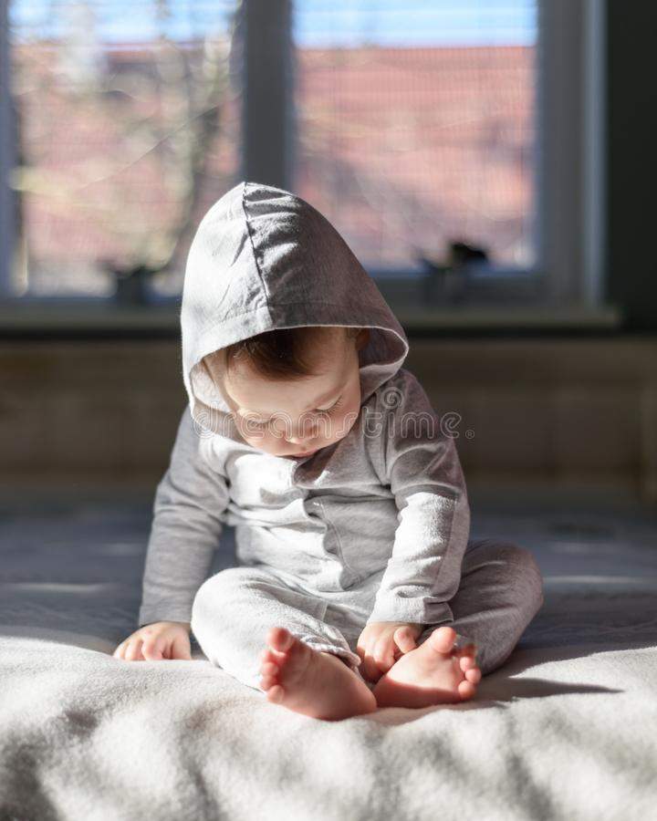 Bébé garçon heureux dans des pyjamas gris photos stock