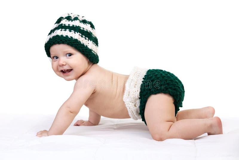Bébé garçon heureux dans le chapeau tricoté rampant au-dessus du blanc photos stock