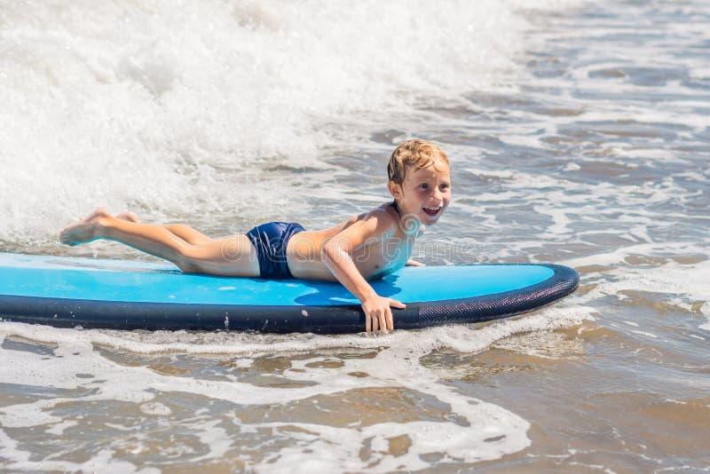 Bébé garçon heureux - jeune tour de surfer sur la planche de surf avec l'amusement sur la mer photographie stock libre de droits