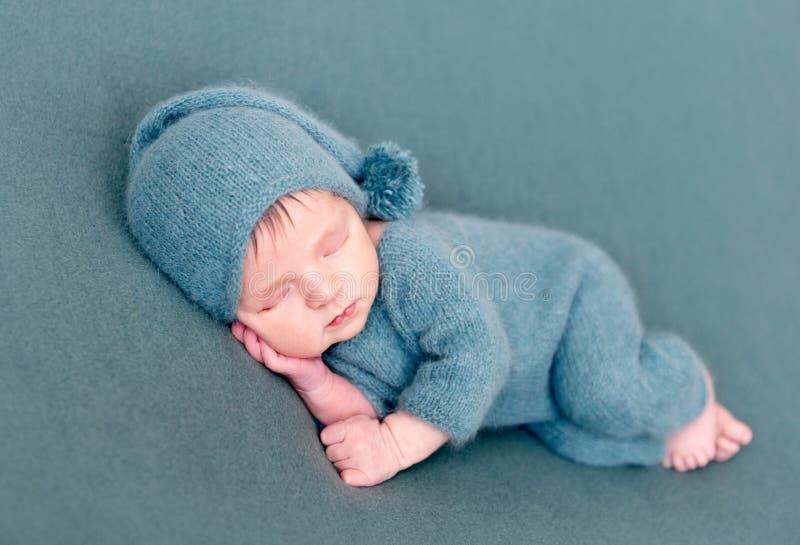 Bébé garçon infantile dormant dans le costume de laine avec les pieds nus image libre de droits