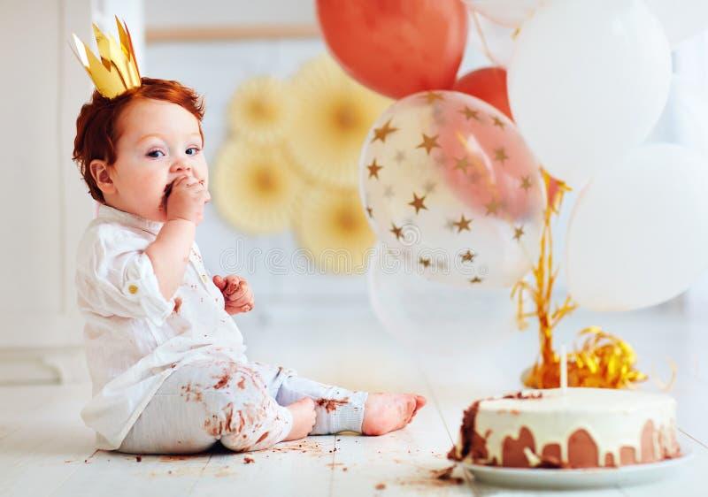 Bébé garçon infantile drôle goûtant son 1er gâteau d'anniversaire photos stock