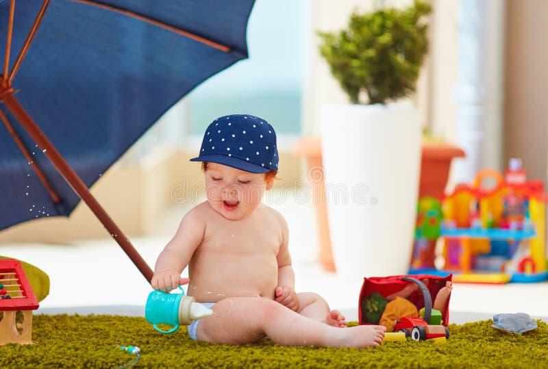 Bébé garçon infantile enthousiaste ayant l'amusement dehors, éclaboussant l'eau de la bouteille au jour d'été chaud photo stock