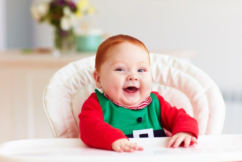Bébé garçon infantile heureux mignon dans le costume d'elfe se reposant dans le highchair photographie stock libre de droits