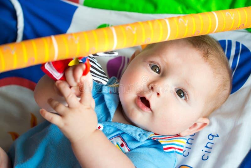 Bébé garçon infantile jouant sur le tapis d'activité photo stock