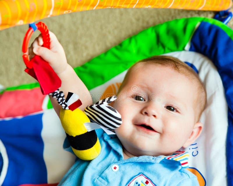 Bébé garçon infantile jouant sur le tapis d'activité photo libre de droits