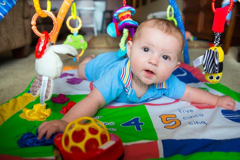 Bébé garçon infantile jouant sur le tapis d'activité photographie stock libre de droits