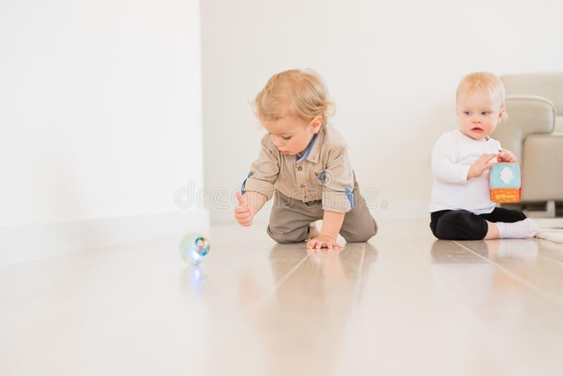 Bébé garçon infantile mignon rampant sur le plancher à la maison et jouant avec la boule colorée photos libres de droits