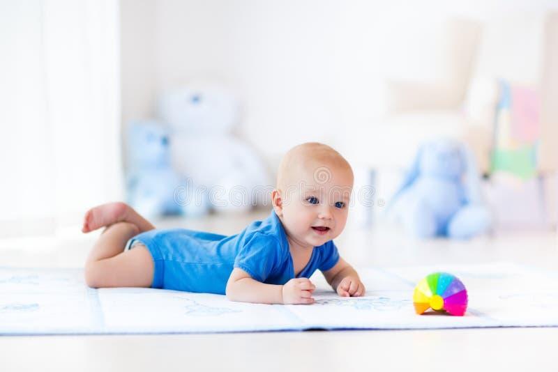 Bébé garçon jouant avec la boule de jouet image libre de droits