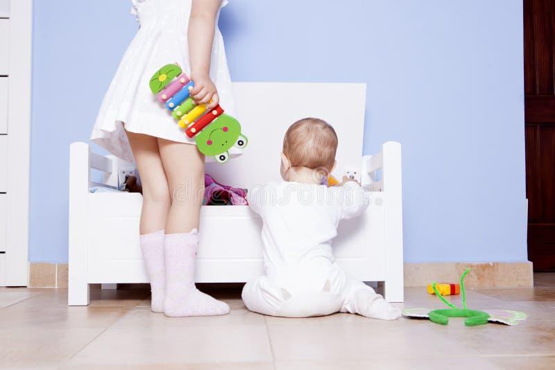 Bébé garçon jouant avec sa soeur à la pièce de jouets photos libres de droits