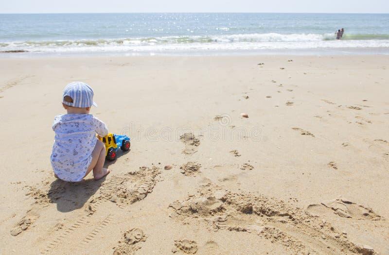 Bébé garçon jouant sur le sable tandis que d'autres enfants éclaboussent à coté image libre de droits