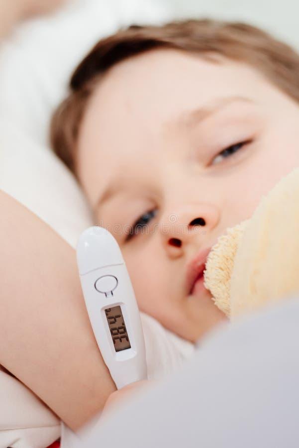 Bébé garçon malade dans le lit avec un thermomètre images stock