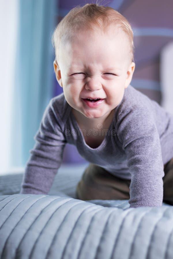 Bébé garçon mignon avec l'expression drôle de visage looing à l'appareil-photo Un enfant infantile fait un visage Strabisme du ga images stock