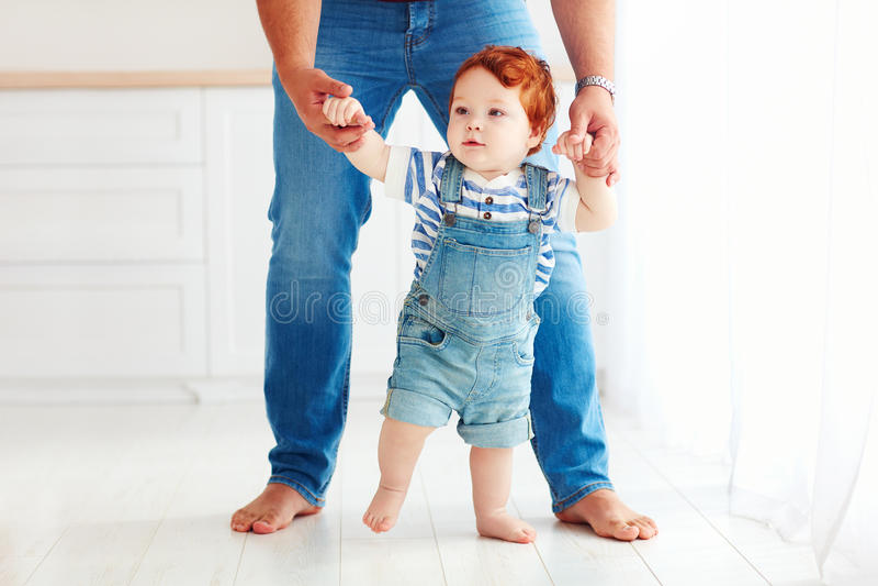 Bébé garçon mignon d'enfant en bas âge apprenant à marcher avec l'aide du père photo stock