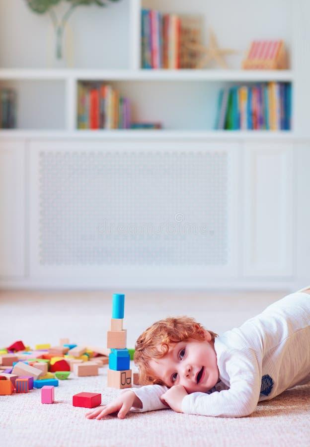 Bébé garçon mignon d'enfant en bas âge jouant avec les blocs en bois, construisant une tour à la maison photos stock