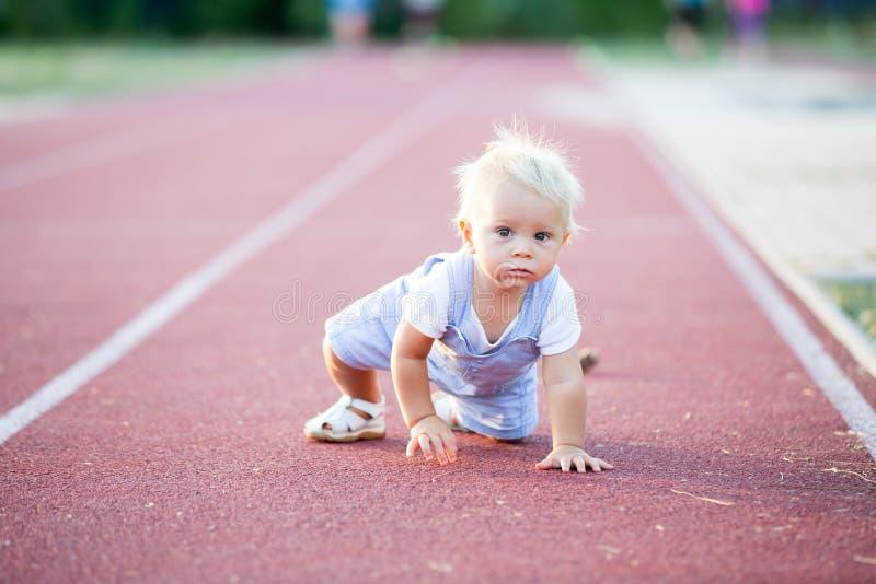Bébé garçon mignon d'enfant en bas âge sur un chemin courant sur un stade images libres de droits