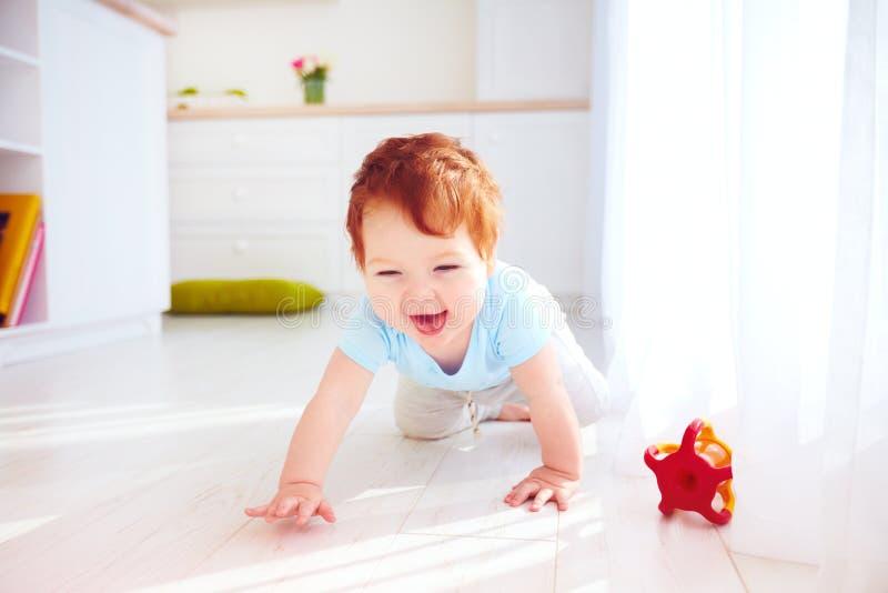 Bébé garçon mignon de gingembre rampant sur le plancher à la maison image libre de droits