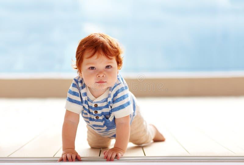 Bébé garçon mignon de gingembre rampant sur le plancher photo libre de droits