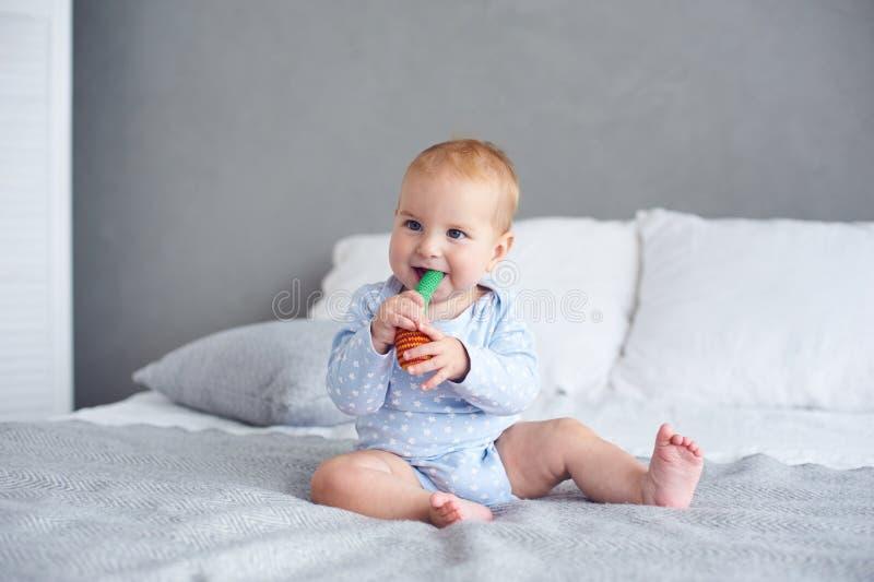 Bébé garçon mignon jouant avec le jouet tricoté sur le lit à la maison photo libre de droits