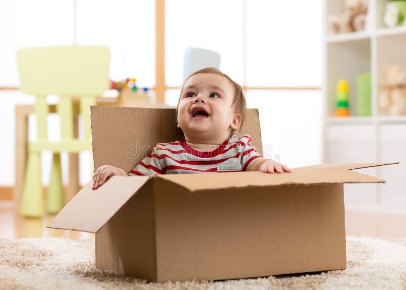 Bébé garçon mignon s'asseyant à l'intérieur de la boîte en carton brune image stock